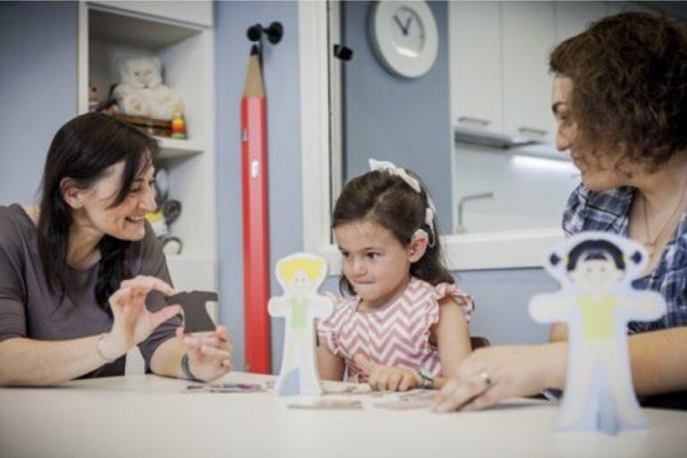 Dos mujeres haciendo test de audiología a niña