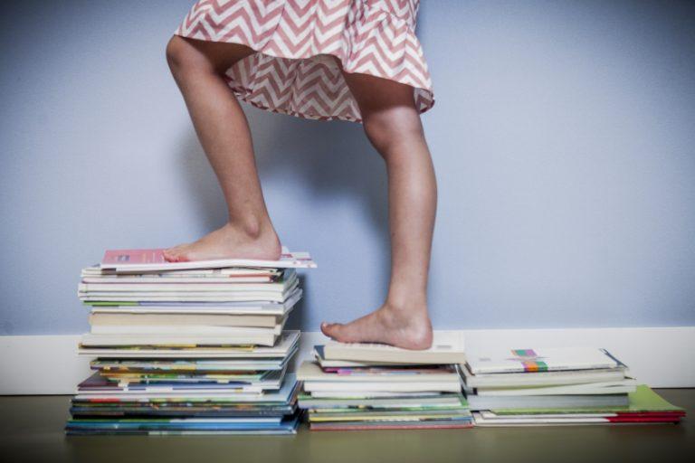 Niña subiendo sobre libros