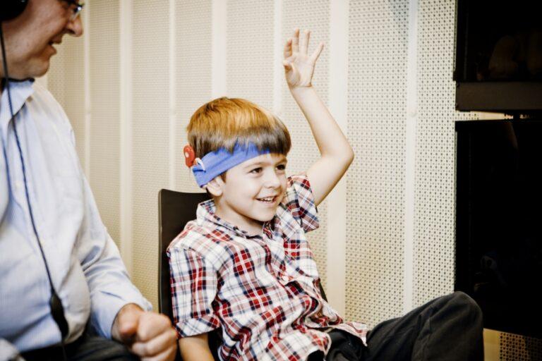 Niño con implante coclear levantando la mano