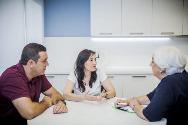 Conversación de tres personas sobre mesa