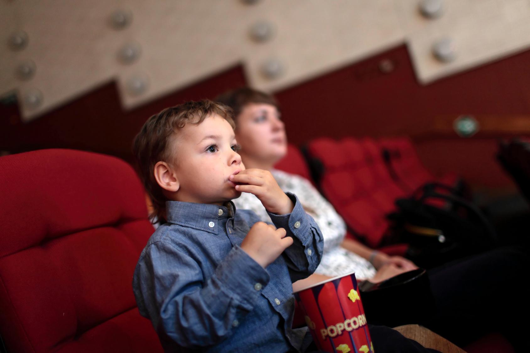 Niño comiendo palomitas en el cine