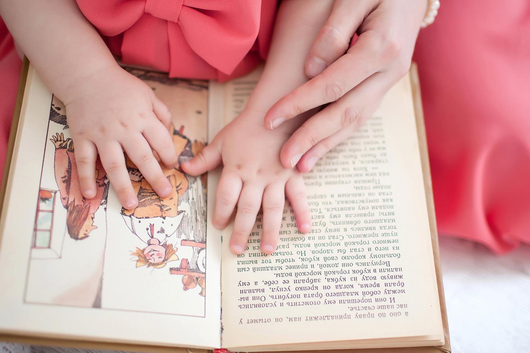 Manos de madre e hija sobre libro