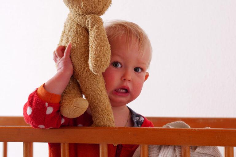 Bebé asustado con peluche en las manos