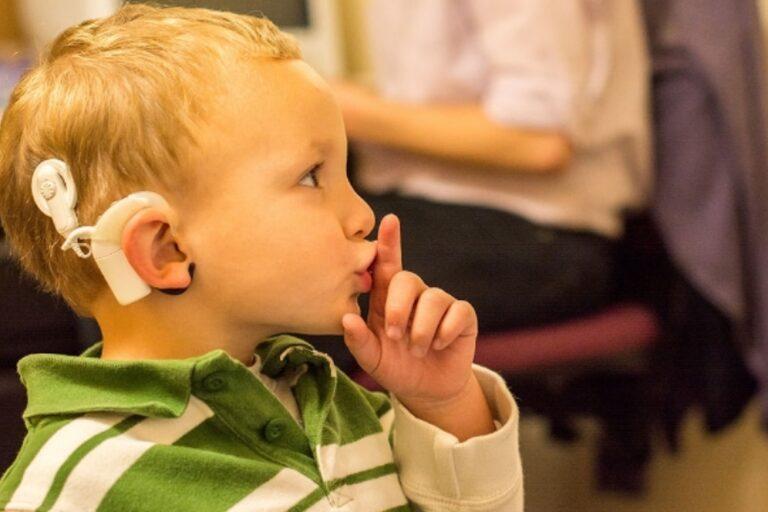 Niño con implante coclear haciendo callar