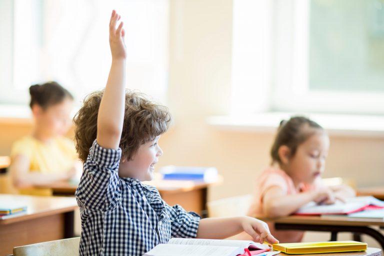 Niño levantando la mano en clases