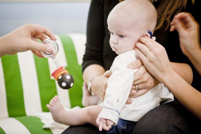 Bebé con audífonos en brazos de madre