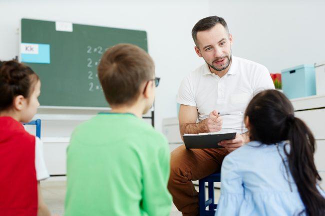 Maestro dando la palabra a niña en clases