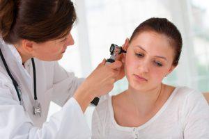 Médica analizando oído de chica joven